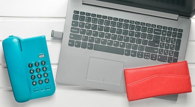 Интернет работа, фриланс концепция. офисный телефон, ноутбук, флэш-накопитель, кошелек на белый деревянный стол. вид сверху. Premium Фотографии