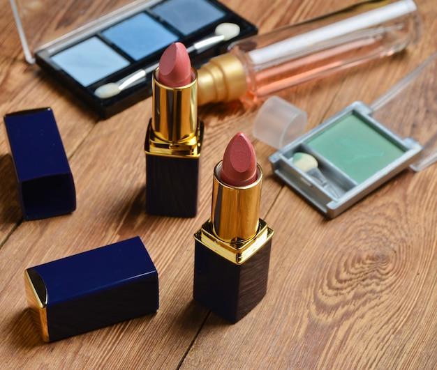 木製のテーブルの女性の口紅とメイクアップ化粧品。 Premium写真
