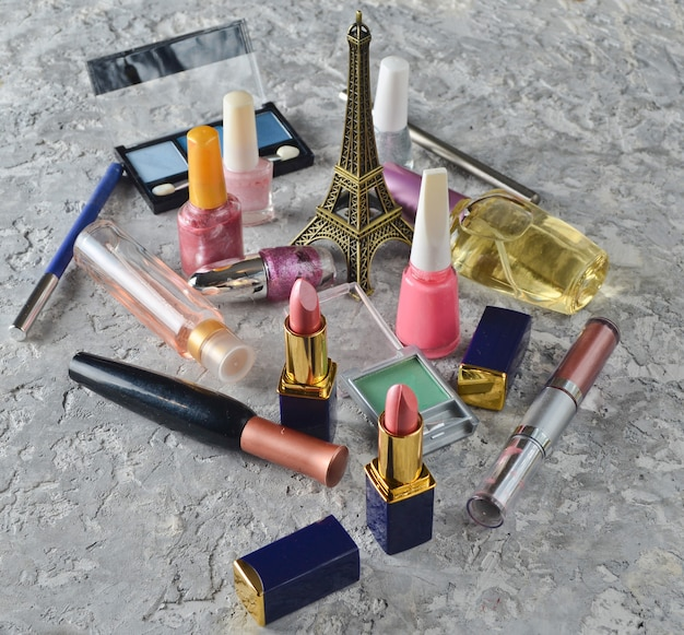メイクアップや美容のための多くの女性用化粧品。マニキュア、香水瓶、化粧品の影、口紅、エッフェル塔の像。 Premium写真