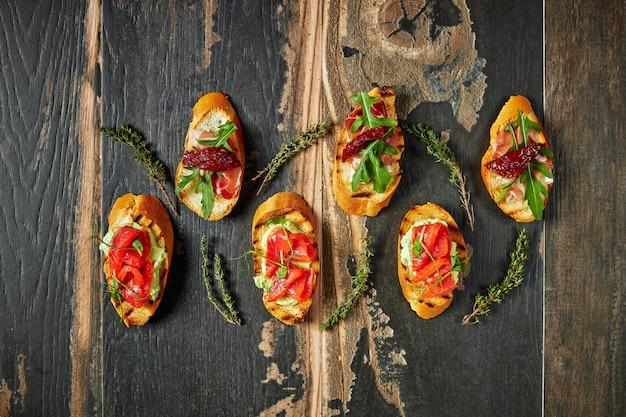 Традиционная брускетта с вяленой пармской ветчиной и прошутто. итальянские закуски набор бутерброды на деревенской деревянной доске вид сверху Premium Фотографии