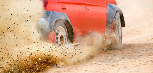 トラック上のラリーレースカーのドリフトからはねかける砂利 Premium写真