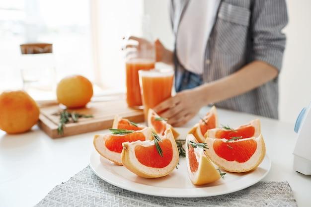 健康的なフィットネスダイエット朝食。デトックスのさわやかなスムージー。スライスしたグレープフルーツに焦点を当てます。女の子の背景。 無料写真