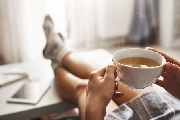 一杯のお茶とチル。ソファに横になっている、コーヒーテーブルに足を抱えている、ホットコーヒーを飲む、朝を楽しんでいる、夢のようなリラックスした雰囲気の女性。特大シャツの女の子が家で休憩を取る 無料写真
