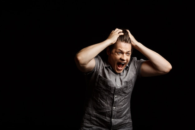 若いハンサムな男が叫んで頭をつかむ 無料写真