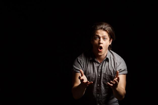 失望した若いハンサムな男が身振りで示す、叫ぶ 無料写真