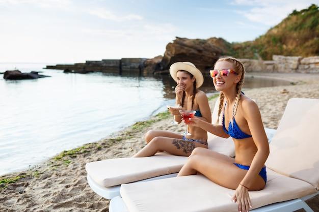 笑顔、日光浴、海の近くの長椅子で横になっている若い美しい女性 無料写真