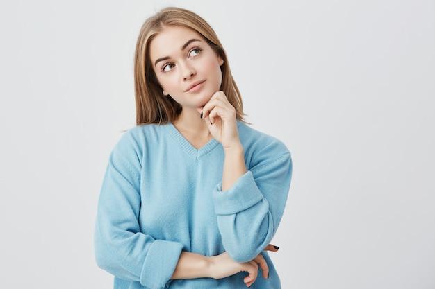 Выражения лица и эмоции. вдумчивая молодая красивая девушка в синем свитере держит руку под головой, с сомнительным взглядом, пока не может решить, какую одежду надеть на вечеринку по случаю дня рождения друга Бесплатные Фотографии