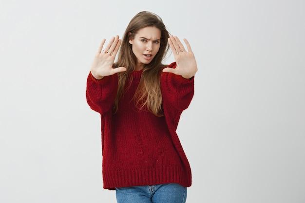 ろくでなし。失望したり侮辱されたりして、止まっているか十分なジェスチャーでカメラに向かって手を引いてゆるいセーターを着てイライラする深刻な人気のある女性の肖像画 無料写真