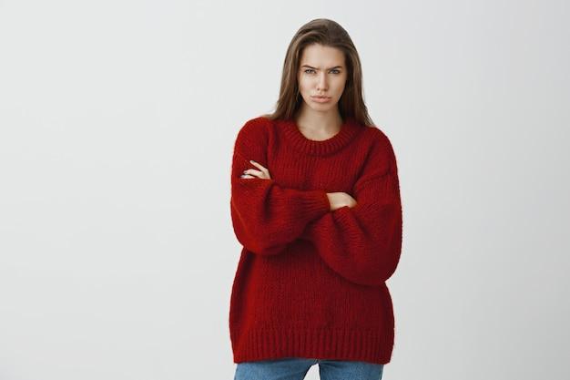 不機嫌で嫉妬を感じる貪欲な魅力的なガールフレンド。赤い緩いセーター、眉をひそめ、やめなさい、イライラして怒って、組んだ手で立っている気分を害したヨーロッパの女性の肖像画 無料写真
