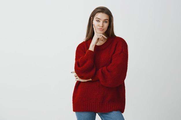 スタイリッシュなルーズセーターで無関心な印象のない魅力的なフェミニンなヨーロッパの女性の肖像画 無料写真
