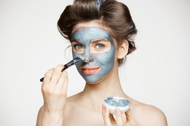 マックで覆っている顔を笑ってヘアカーラーで若くてきれいな女性。フェイシャルトリートメント。美容美容とスパ。 無料写真
