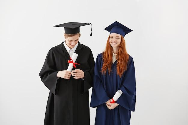 持株卒業証書を笑顔のマントルで大学の幸せな卒業生。 無料写真