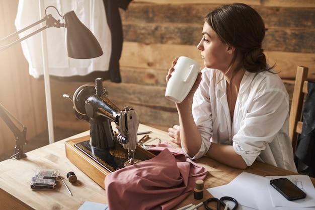 ワークショップの別の日が終わりました。ミシンのそばに座ってお茶を飲んだり、仕事を休んだりしながら脇をよそ見する夢のような思慮深い女性の下水道。デザイナーがホットコーヒーで充電 無料写真