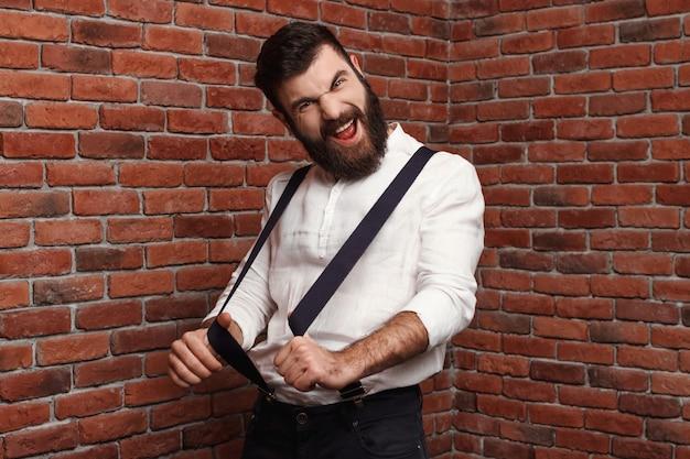 レンガの壁でポーズを喜んで若いハンサムな男。 無料写真