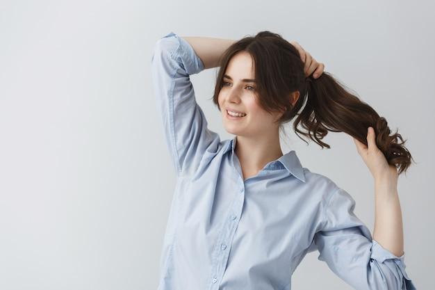 幸せな顔の表情で早朝外出の準備をして、髪型を作る若いハンサムな白人少女。 無料写真