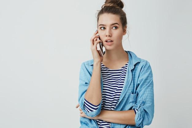 Здравствуйте, я могу заказать. портрет милой повседневной симпатичной модной женщины, смотрящей в сторону, задумчиво держа смартфон прижал ухо, разговаривая, заказывая столик в ресторане через мобильный телефон Бесплатные Фотографии