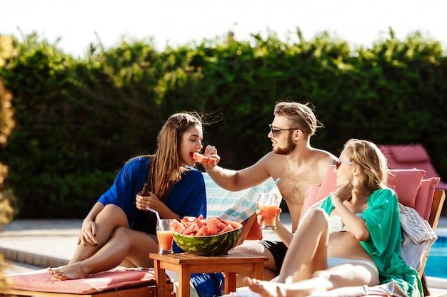 友達の笑顔、スイカを食べる、カクテルを飲む、スイミングプールのそばでリラックス 無料写真