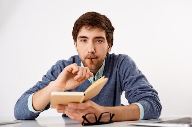 Вдумчивый, творческий мужчина журналист или писатель, кусает карандаш, держит тетрадь, пишет график, выглядит мышлением Бесплатные Фотографии
