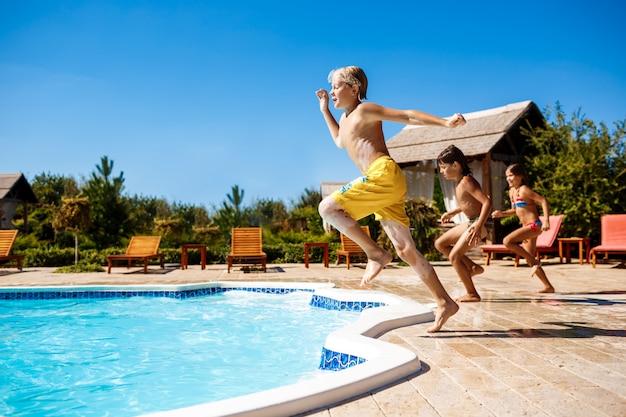 陽気な子供たちは、喜び、ジャンプ、プールで泳いでいます。 無料写真