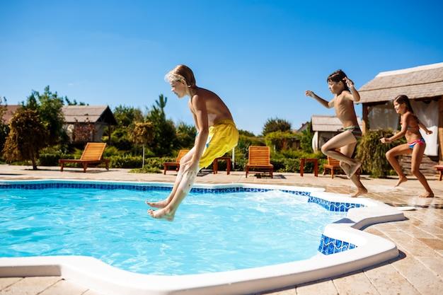 Веселые дети радуются, прыгают, купаются в бассейне. Бесплатные Фотографии