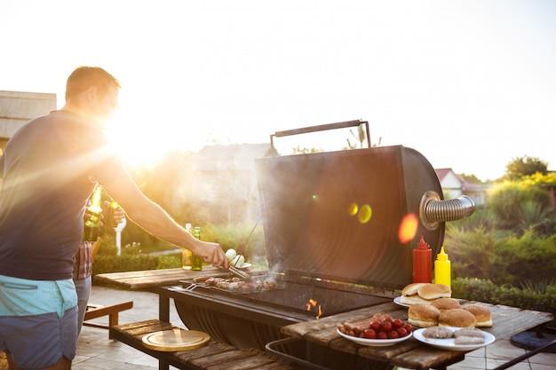 若い男性は、コテージの田舎でグリルでバーベキューを焙煎します。 無料写真