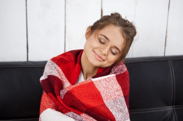 笑みを浮かべて、ソファーに座っていた格子縞の若い美しい女性。 無料写真