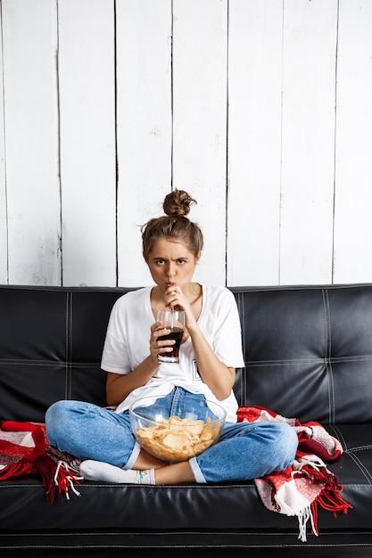 チップを食べる、ソーダを飲む、テレビを見る、ソファーに座っている女性。 無料写真
