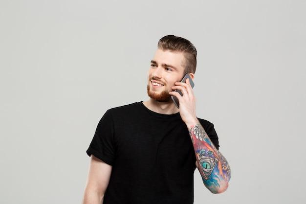 灰色の壁を越えて電話で話す若いハンサムな男。 無料写真
