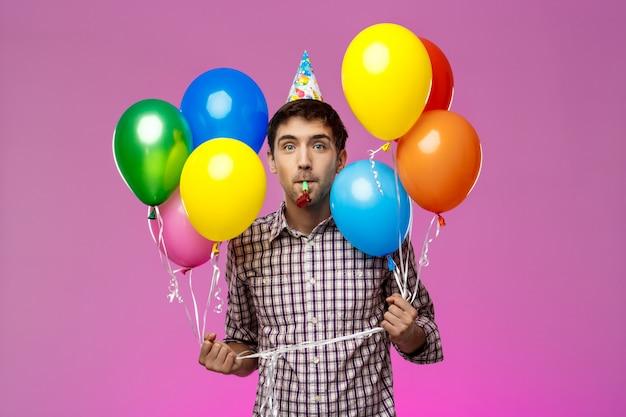Молодой человек празднует день рождения, держа красочные шарики над фиолетовой стеной. | Бесплатно Фото