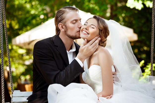 笑顔、キス、公園のブランコに座っている若い美しい新婚夫婦。 無料写真