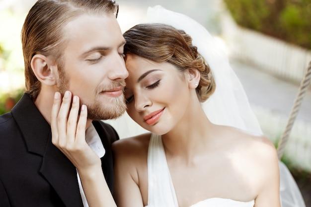 目を閉じて笑って楽しんで若い美しい新婚夫婦。 無料写真