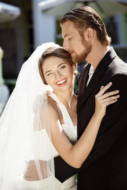 幸せな美しい新婚夫婦が笑みを浮かべて、抱きしめ、外でキスします。 無料写真