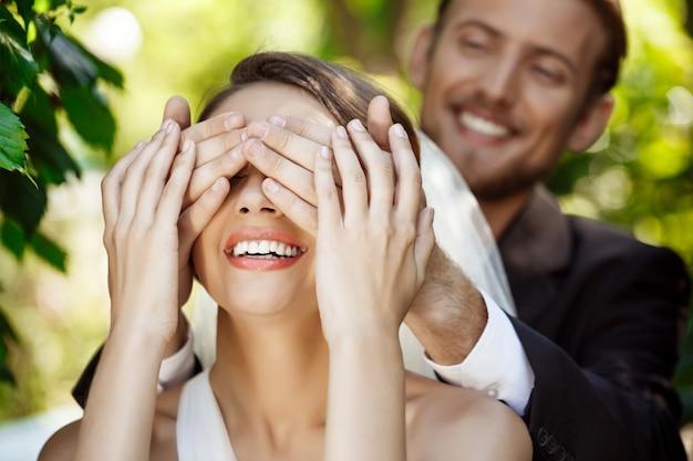 笑顔の新婚夫婦のカップル。手で花嫁の目を覆っている新郎。 無料写真