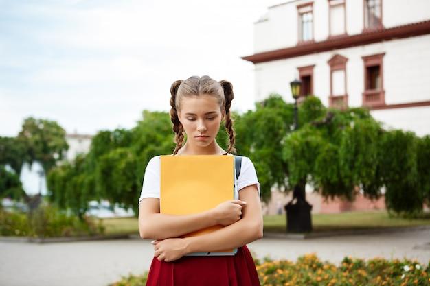 屋外保持フォルダーを見下ろして動揺の若い美しい女子学生 無料写真