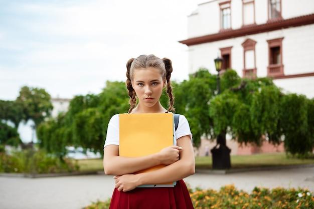 屋外でフォルダーを探して保持している動揺の若い美しい女子学生 無料写真