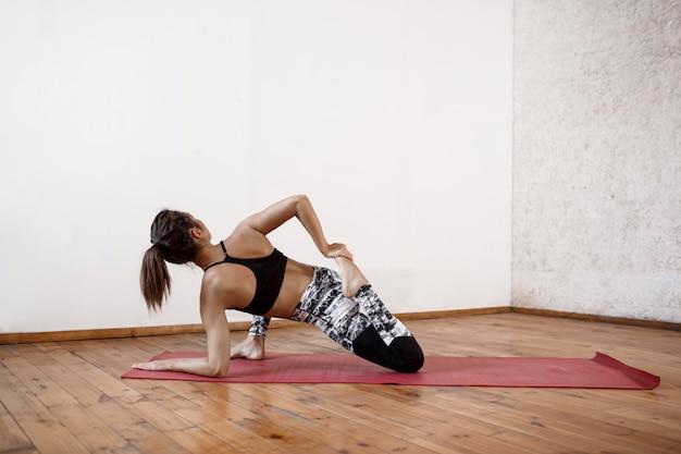 赤いマットで屋内ヨガを練習して若い運動美人 無料写真