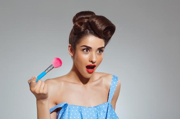 Портрет красивой очаровательной женщины, держащей кисть для макияжа Бесплатные Фотографии