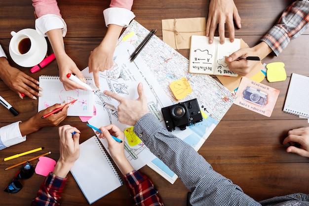 ドキュメントと下書きで木製のテーブルにビジネスマンの手 無料写真