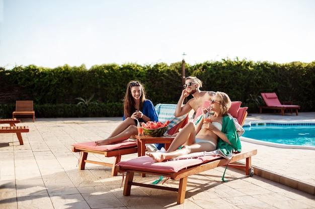 友達の笑顔、休憩、カクテルを飲み、スイミングプールのそばに横たわって 無料写真