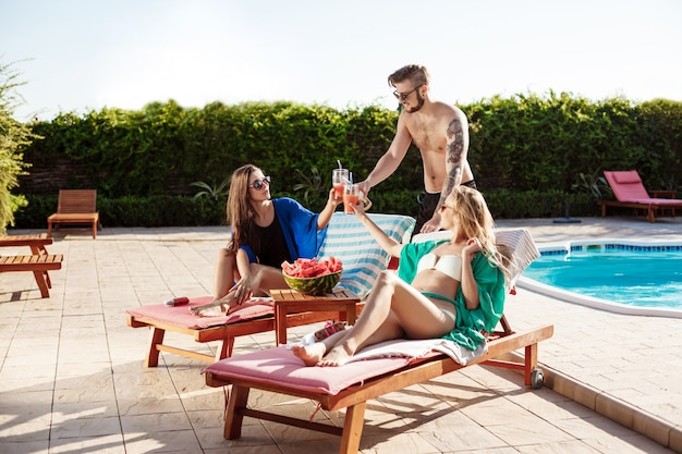 友達の笑顔、日光浴、カクテルを飲み、スイミングプールのそばに横たわって 無料写真