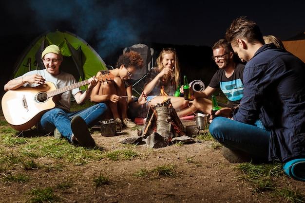 たき火のそばに座って、笑顔で、話して、休んで、ギターを弾く友人 無料写真