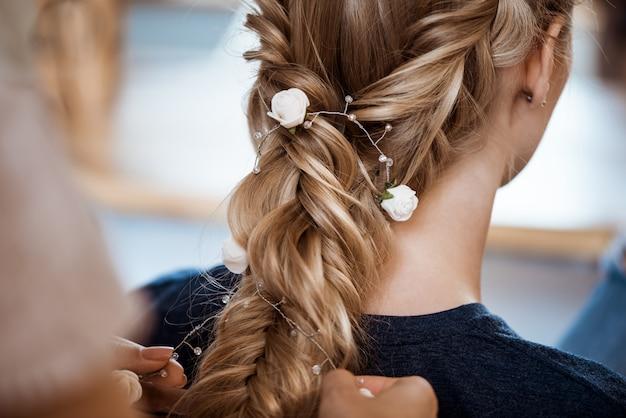 ビューティーサロンで金髪の女性に髪型を作る女性美容師 無料写真