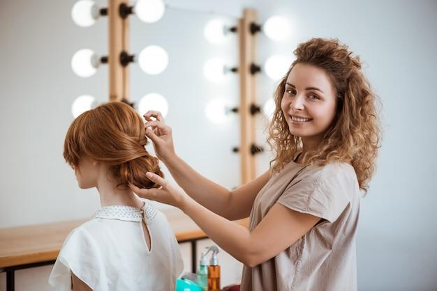 ビューティーサロンで赤毛の女性に髪型を作る笑顔の女性美容師 無料写真