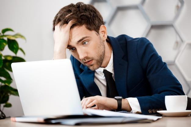 ノートパソコン、オフィスの背景に座っている青年実業家を混乱させます。 無料写真