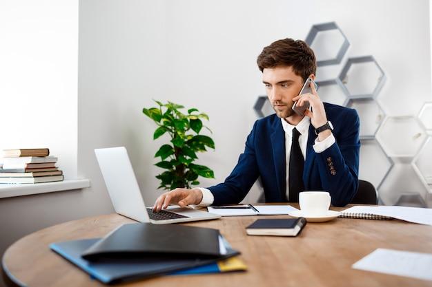 電話、オフィスの背景で話す若い成功した実業家。 無料写真