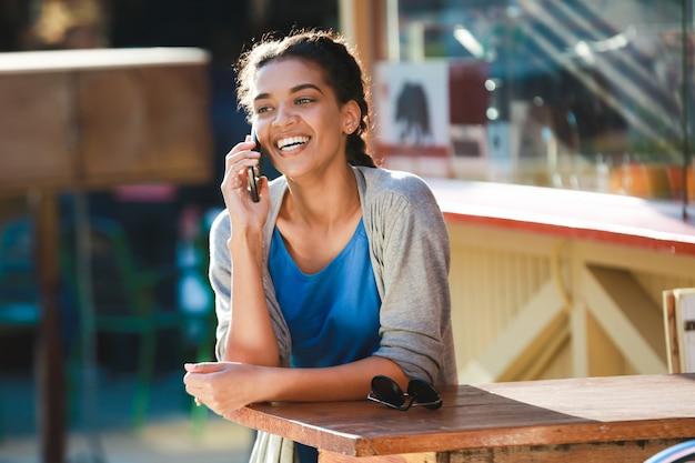 電話で話している美しい陽気な暗い肌の女の子 無料写真