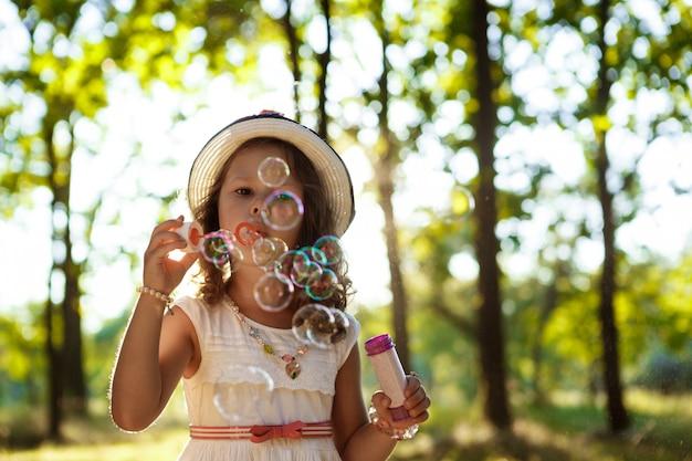Молодая красивая девушка дует пузыри, прогулки в парке на закате. Бесплатные Фотографии