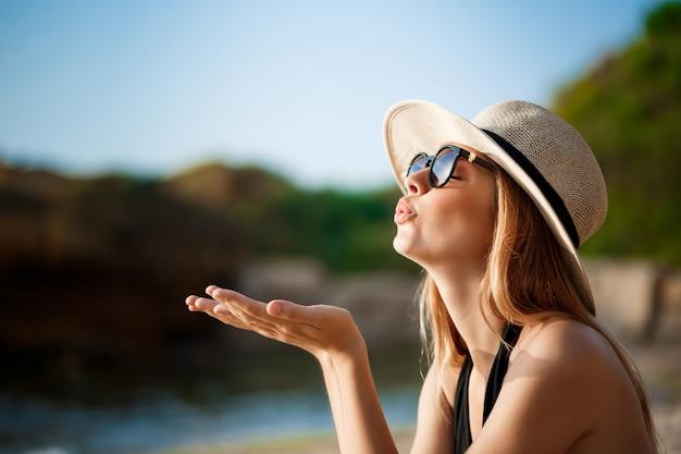 メガネと帽子を身に着けている美しい陽気な少女は朝のビーチにかかっています。 無料写真