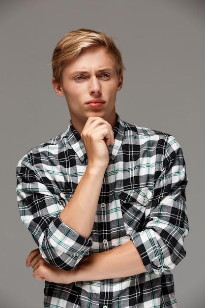 灰色の壁を離れて胸を組んで手でカジュアルな格子縞のシャツを着て自信を持って金髪のハンサムな若い男 無料写真