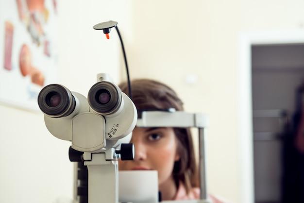 黄色の壁の上に座って、検眼医のオフィスに座って、顕微鏡で彼女の視力を確認する手順の開始を待っているかわいい白人女性患者の肖像画。眼科のコンセプト 無料写真